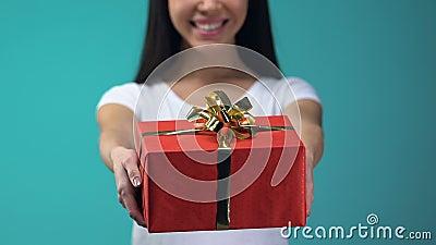 Contenitore di regalo allegro di rappresentazione della ragazza alla macchina fotografica, isolata su fondo blu, feste archivi video