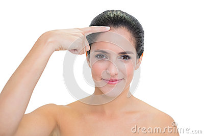 Content bare brunette pointing at forehead