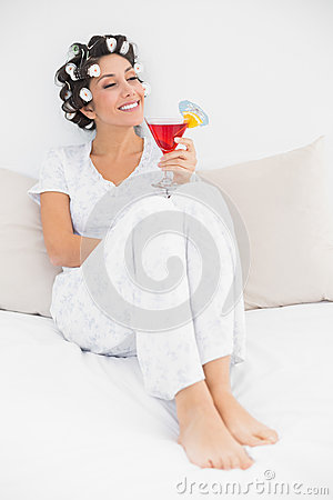 Content brunette in hair curlers sitting on her bed holding a cocktail