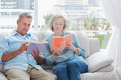 Content couple reading books on the couch