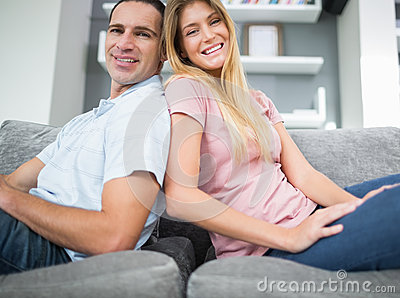 Content couple sitting back to back on the couch together