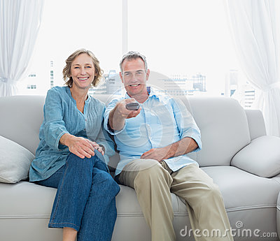 Content middle aged couple sitting on the couch watching tv