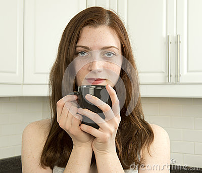Contented young woman with cup of tea or coffee