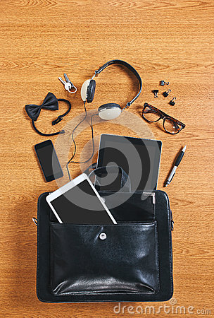 The contents of a modern business briefcase on a wooden desk.