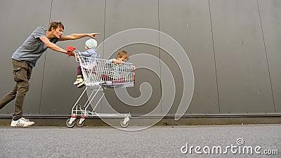 Contexte commercial Un beau père avec des enfants dans le chariot à provisions, un chariot poussant vers l'avant Magasiner avec banque de vidéos