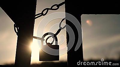Contra el cielo y el sol en la puesta del sol cuelga en las cadenas de un candado viejo y oxidado almacen de metraje de vídeo