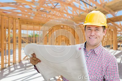 Contractor With Plans On Site Inside New Home Construction Framing. Stock Photo