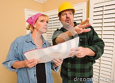 Contratista en sombrero duro que discute planes con la mujer