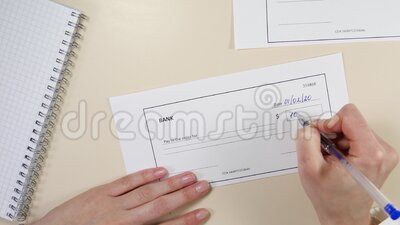 Controllo bancario Una donna scrive un assegno in banca per mille dollari archivi video