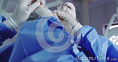 Controllo di un medico femmina che aiuta il medico a indossare una maschera chirurgica in sala operatoria archivi video