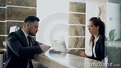 Convidado do homem de negócios que falam com a menina do recepcionista que está na mesa na recepção do hotel e conta pagando com  vídeos de arquivo