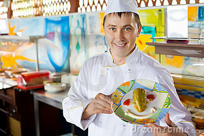 Cook holding dish with salad in form of smile