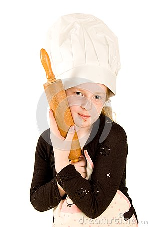 Cook wearing a chefs hat is holding a rolling pin