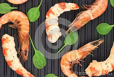 Cooked unshelled shrimp on frying pan.