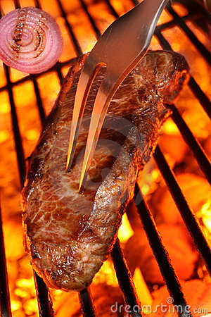Cooking a beef steak on a barbecue grill