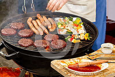 Cooking burgers and sausages on barbecue