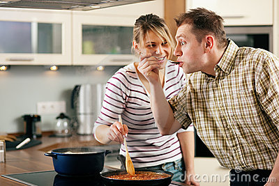Cooking couple - tasting the sauce