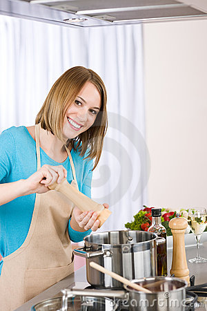 Cooking - Happy woman by stove in kitchen