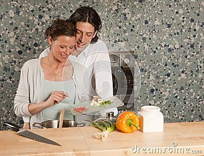 Cooking he looks over her shoulder