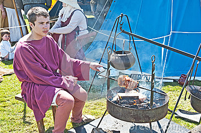 Cooking meat in a medieval re-enactment Editorial Stock Photo