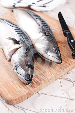 Cooking raw mackerel fish on cutting board