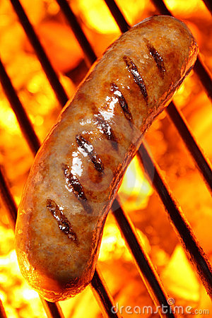 Cooking a sausage hot dog on barbecue grill