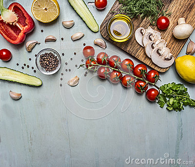 Cooking vegetarian food oil, mushrooms, cherry tomatoes on a branch, cucumber, pepper, seasoning on wooden rustic background top v Stock Photo