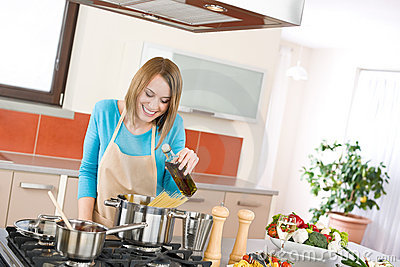Cooking - Young woman with spaghetti on stove