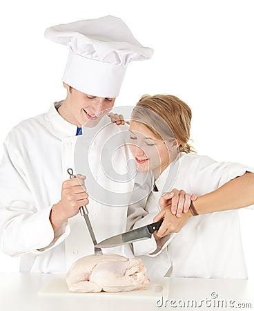 Cooks team preparing raw chicken