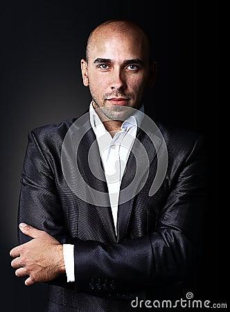 Cool businessman standing on dark gradient