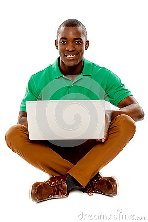 Cool guy seated on floor using laptop