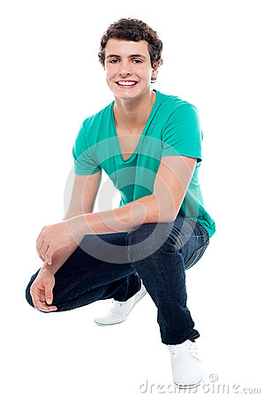 Cool guy wearing white sneakers, squatting posture