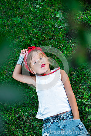 Free Cool Little Girl Outdoor Lying On The Grass. Child In White T-shirt, Jeans Shorts, Red Necklace And Bandage On The Head. Summer. Stock Photography - 97581842