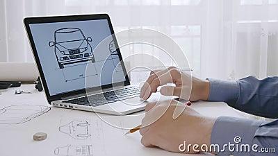 Coordenador que trabalha em um esboço do projeto do carro usando seu laptop vídeos de arquivo