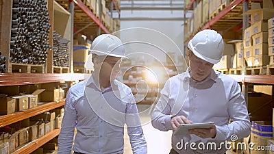 Coordenadores masculinos no funcionamento do capacete de segurança no canteiro de obras da fábrica do centro da logística, dois d video estoque