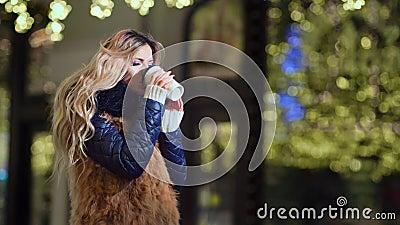 Copo de papel quente bebendo de aquecimento fêmea do café exterior no fundo amarelo das luzes do bokeh do brilho vídeos de arquivo