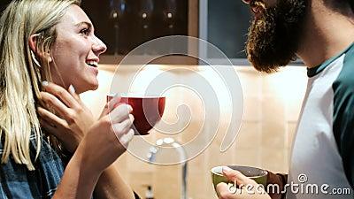 Coppia baciare mentre mangiano il caffè in cucina 4k video d archivio