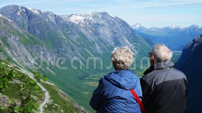 Coppia senior in vacanza in montagna Uomo maturo e donna che si gode la vista di una valle verde e di montagne con la neve video d archivio