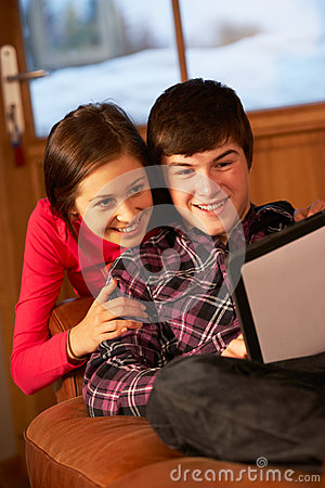 Coppie adolescenti che si distendono con il calcolatore del ridurre in pani