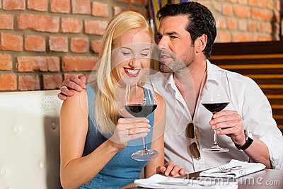 Coppie attraenti che bevono vino rosso in ristorante