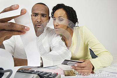 Coppie che esaminano la ricevuta di spesa a casa