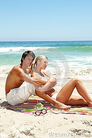 Coppie che si siedono insieme alla spiaggia