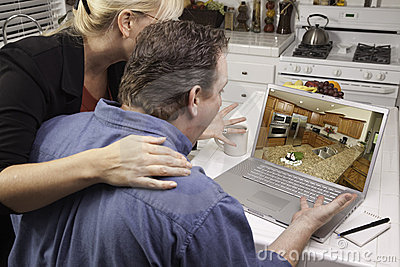 Coppie in cucina per mezzo del computer portatile - miglioramento domestico