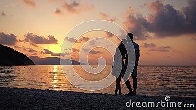 Coppie nell'amore che si abbraccia che sta su una spiaggia al tramonto sopra il mare archivi video