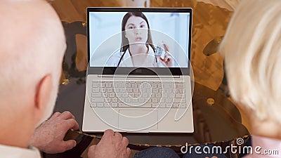 Coppie senior a casa che hanno video consultazione di chiacchierata via la chiamata di app del messaggero sul computer portatile  archivi video