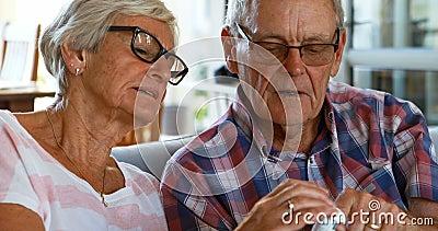 Coppie senior che discutono farmaco sul sofà 4k archivi video