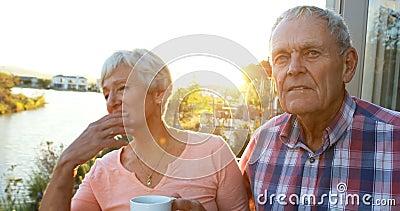 Coppie senior con la condizione della tazza di caffè nel balcone 4k video d archivio