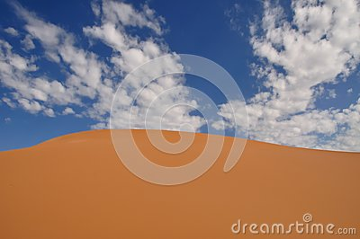 Coral pink sand dune and blue sky with white clouds