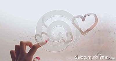 Corazones del dibujo de la mano con los fingeres en ventana cocida al vapor en un primer del día lluvioso metrajes