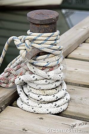 Corda atada em torno de um poste de amarração do navio